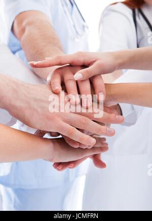 Ärzte und Krankenschwestern in ein medizinisches team Stapeln Hände in einer Show der Zusammenarbeit und Solidarität, - Stockfoto