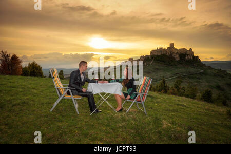 Paar in Liebe trinken roten Wein in der Natur unter den Ruinen einer Burg bei Sonnenuntergang. - Stockfoto