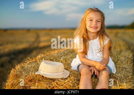 Kleines Mädchen in einem Feld mit Heu rollt bei Sonnenuntergang - Stockfoto