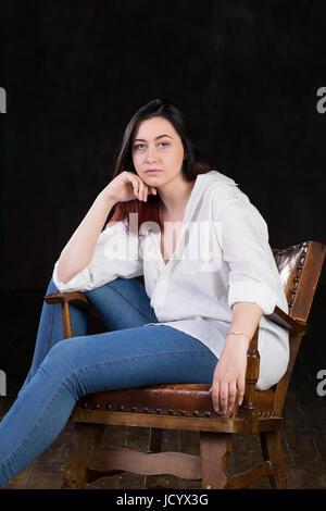 Schöne weiße braune kurzhaarige Hündin mit farbigen in roten enden tragen Männer weißes Hemd und blaue Jeans, sitzt - Stockfoto