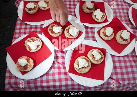 Scones mit Sahne und Marmelade auf Papptellern auf einem Tisch in einem roten und weißen Kunststoff Tischdecke bedeckt. - Stockfoto