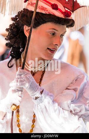 Nahaufnahme von Frau, 30 s, Gesicht drehte sich zur Seite zu schauen. In viktorianischen Kostüm gekleidet und mit einer Sun Parasol (nicht gesehen). Gekräuselte schwarze Haare, Mund beim Sprechen. Stockfoto