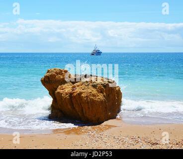 Wellen Waschen um einen Felsen am Praia Dona Ana und Yacht im Hintergrund, Algarve, Portugal - Stockfoto