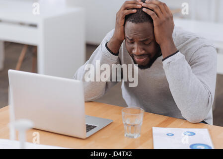 Trostlos launisch Mann leidet unter Kopfschmerzen - Stockfoto