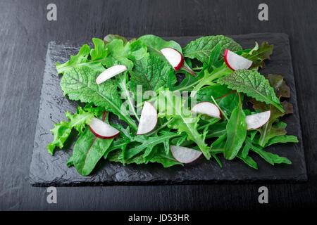 Gemischte Salatblätter mit Radieschen auf schwarzem Schiefer Teller. Closae oben - Stockfoto