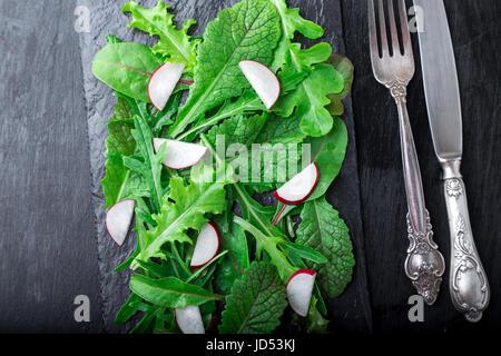 Gemischte Salatblätter mit Radieschen auf schwarzem Schiefer Teller. Ansicht von oben