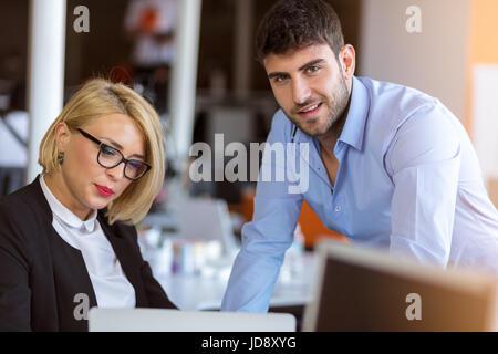 Kollegen unterhalten, zusammen sitzen am Bürotisch, Lächeln - Stockfoto