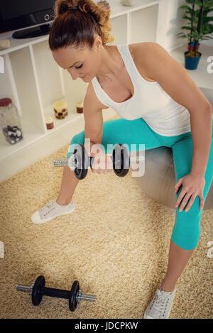Schöne junge Frau, die Übung mit Hanteln zu Hause. - Stockfoto