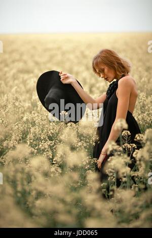 Junge Frau im schwarzen Kleid und Hut in der Hand unter den blühenden Wiese. Sie schaut nachdenklich. - Stockfoto
