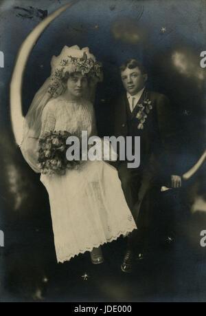 Antike c1910 Fotografie, Studio-Porträt einer Braut und Bräutigam auf einer Mondsichel. Lage ist wahrscheinlich - Stockfoto