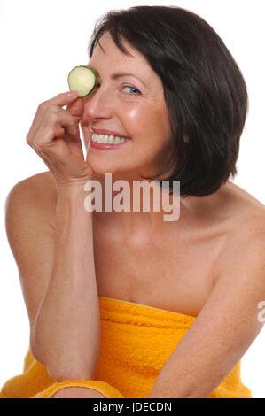 Portrait von glücklich senior Frau mit Gurke. Schönheit und Pflege-Konzept - Stockfoto