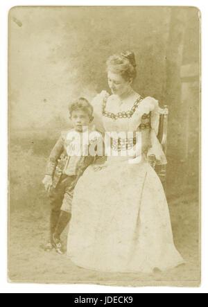 Viktorianische Kabinett Karte Foto (Zuschneiden, die an der Basis) einer attraktiven Dame trägt einen schönen Sommer Kleid mit Ärmel, stolz ihr Sohn, der in Latzhosen und Rüschen Hemdkragen und Samt Jacke gekleidet ist - eine Art und Weise, indem der kleine Lord Fauntleroy Roman inspiriert von Frances Hodgson Burnett. im Jahr 1885 veröffentlicht - 1886. Aus dem Jahre 1890 Stockfoto