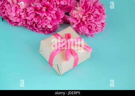 Schöne frische rosa Pfingstrose Blüte mit Geschenk-Box auf Minze Hintergrund. Pfingstrosen-Sommer. - Stockfoto