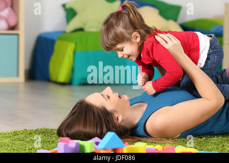 Glückliche Mutter mit ihrer Tochter auf einem grünen Teppich im Schlafzimmer zu Hause liegen spielen - Stockfoto