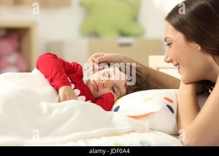 Liebevolle Mutter, die ihr Kleinkind Mädchen schlafen in einem Bett in ihrem Zimmer zu Hause betrachten - Stockfoto