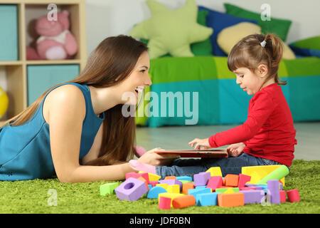 Seitenansicht einer Mutter und Kleinkind spielen mit einem Buch auf einem Teppich im Schlafzimmer zu Hause sitzen - Stockfoto