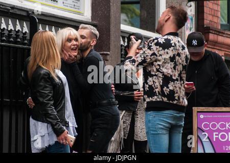 Schauspielerin Sherrie Hewson ist gefangen von treuen Fans für ein Foto-Shooting in Canal Street Manchester - Stockfoto