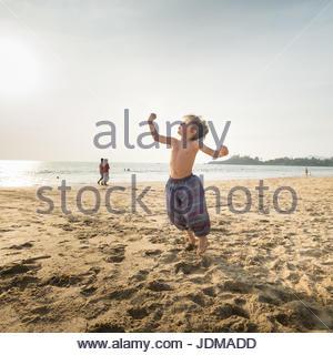 Eine europäische junge beugen Sie seine Muskeln beim Springen auf einem Strand in Indien. - Stockfoto