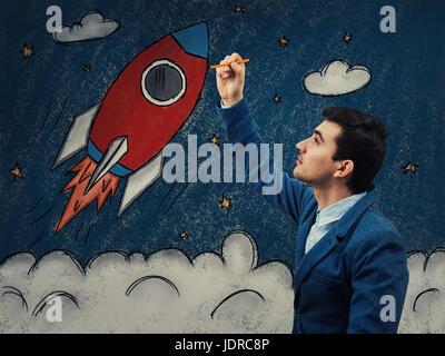 Junger Geschäftsmann mit einem Bleistift in der Hand, die Zeichnung als eine Rakete abheben im Kosmos. Business - Stockfoto
