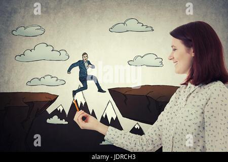 Lächelnde Frau mit einem Bleistift in der Hand zeichnen einen skizzierten Geschäftsmann über einem Abgrund Hindernis - Stockfoto
