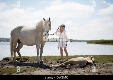 Mädchen Petting Pferde am Sandstrand - Stockfoto