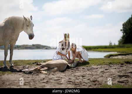 Mädchen streicheln Pferd am Sandstrand - Stockfoto