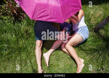 Eltern und Sohn liegen auf dem Rasen unter rosa Regenschirm - Stockfoto