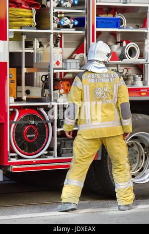 Feuerwehrmann tragen Helme stehen neben Feuerwehrauto, Genf, Schweiz - Stockfoto