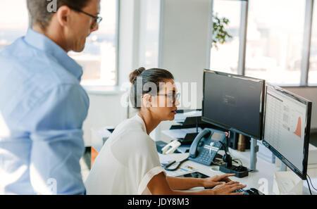 Reife Geschäftsfrau arbeiten am Computer mit männlicher Kollege bereitzustehen. Business-Mann und Frau am Schreibtisch, - Stockfoto
