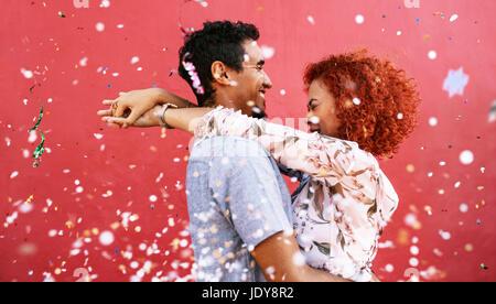 Junge Frau umarmt Man mit geschlossenen Augen vor einem roten Hintergrund. Junges Paar in der Mitte regnet Konfetti - Stockfoto