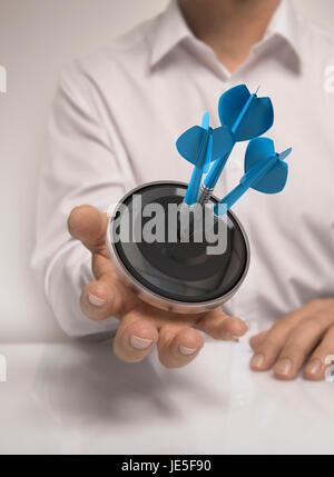 Mann Hand, die ein Ziel mit drei Darts schlagen die Mitte, blau und Beige Töne, Konzept-Bild zur Veranschaulichung - Stockfoto