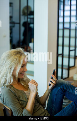Reife Frau entspannend mit smartphone - Stockfoto