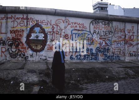 Eine Frau liest die Graffiti auf der Berliner Mauer, während DDR Grenze wachen Blick auf. Berlin 1987 - Stockfoto