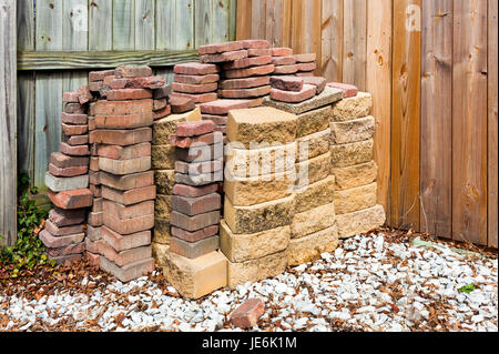 Gebrauchte Ziegel und Pflastersteine gegen Holzzaun mit weißem Kies Vordergrund gestapelt. Horizontale. - Stockfoto