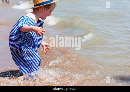 Kaukasische blonde Kind Junge, 4-5 Jahre alt, stehend in der Brandung am Strand, tragen, Stroh, Hut und blaue und - Stockfoto