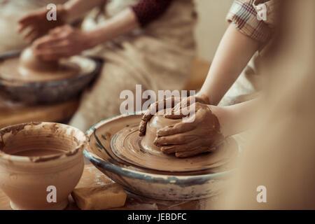 Nahaufnahme eines Kinderhände arbeiten auf der Töpferscheibe in Werkstatt