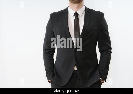 Schließen Sie einen Teil des Geschäfts Körper des Mannes im schwarzen Anzug mit Händen in den Taschen auf weißem - Stockfoto