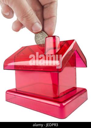 rotes Schweinchen-förmige Haus mit einer Hand eine Silbermünze in ihrem Steckplatz einfügen - Stockfoto