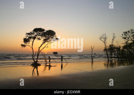 Fischer mit Fischernetz und einsame Baum im goldenen Stunde Sunrise beach Tan Thanh Co Gong Viet Nam - Stockfoto