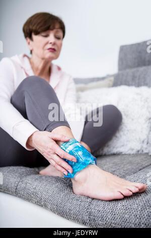 Ältere Frau auf Couch sitzen, Kühlung verstauchten Knöchel - Stockfoto