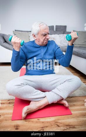 Ältere Mann tut, Muskel training zu Hause - Stockfoto