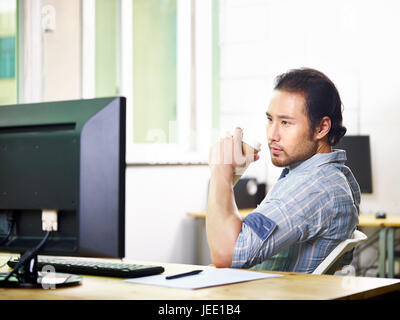 asiatische Geschäftsmann arbeiten im Büro hält eine Tasse Kaffee mit Blick auf Desktop-computer - Stockfoto