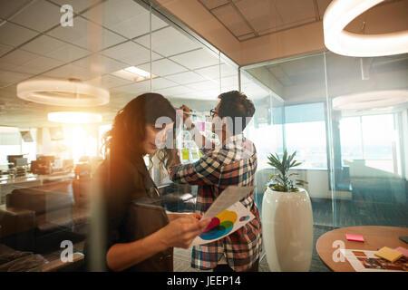 Zwei kreative Profis arbeiten auf neues Projekt. Frau, die an Fotografien und Mann klebt am Papier auf Glaswand - Stockfoto