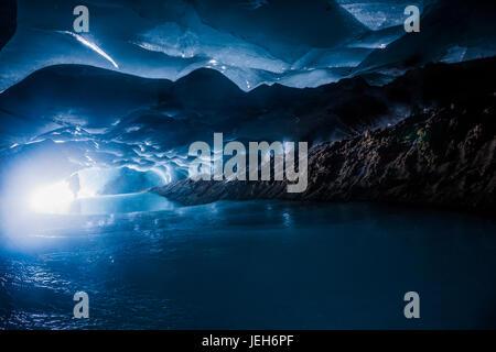 Ein Mann ist am Eingang zu einer dunklen Eishöhle innerhalb Augustana-Gletscher in Alaska Range Silhouette; Alaska, - Stockfoto