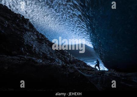 Ein Mann beleuchtet einen dunklen Tunnel unter dem Eis der Canwell Gletscher mit einer Taschenlampe, innen Alaska, - Stockfoto