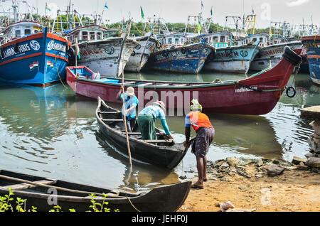 Fischer Druck kleine Boot heraus und bunte Fischerboote; Kadappuram, Kerala, Indien - Stockfoto