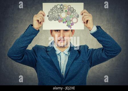 Jungen Mann hält ein Weißbuch über den Kopf mit einem Gehirn verliert seine Farbe, isoliert auf graue Wand Hintergrund - Stockfoto