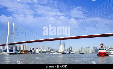 Nanpu-Brücke über den Huangpu-Fluss mit Skyline im Hintergrund, Shanghai, China - Stockfoto