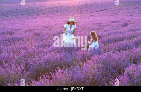 Mutter und Tochter stehen in einem Lavendelfeld, Bulgarien - Stockfoto