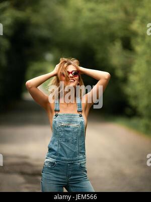 Junge Frau in Denim-Overalls auf Forststraße. Sie steht und lächelt unter Bäumen in Sonnenbrillen. - Stockfoto